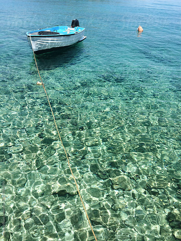 Small fishing boat floating on clear water in Adriatic Sea by Jovana Milanko for Stocksy United