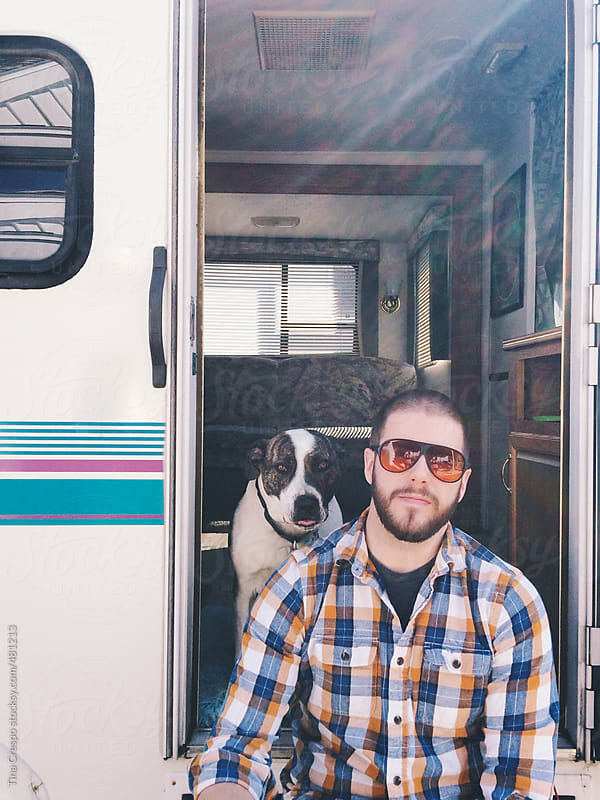 A man with traveling dog by Tina Crespo for Stocksy United