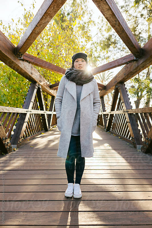 Asian woman standing on a wooden bridge on a sunny winter day. by BONNINSTUDIO for Stocksy United