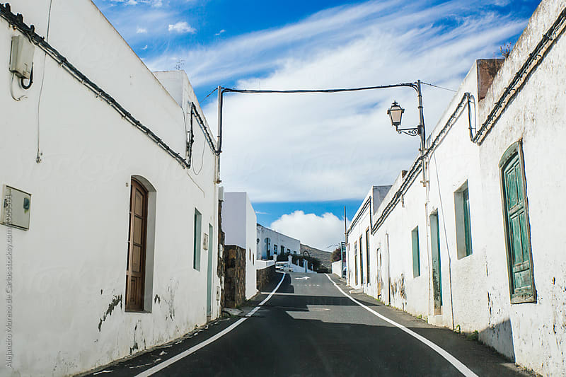 Asphalt road  in old city with white houses by Alejandro Moreno de Carlos for Stocksy United