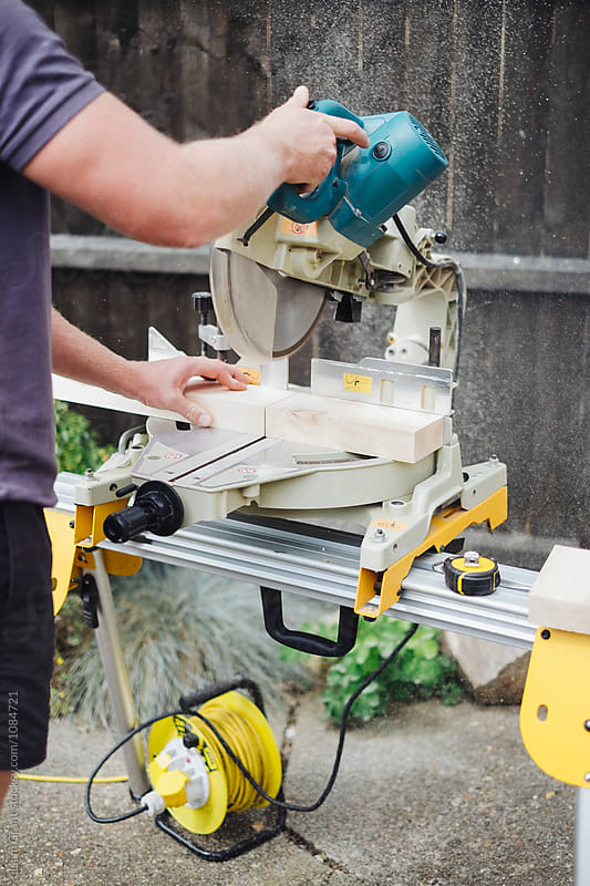 Carpenter cutting wood with a chop saw. UK. by Liam Grant for Stocksy United