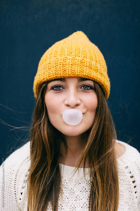 Funny portrait of a beautiful 14 years old girl making bubbles out of a bubble gum. by BONNINSTUDIO for Stocksy United
