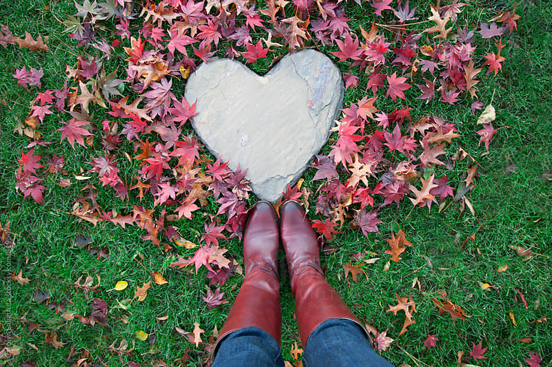 Female in jeans and boots standing above fallen maple leaves and a heart shaped rock by Carolyn Lagattuta for Stocksy United