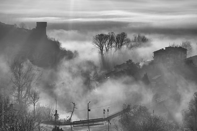Town engulfed by fog by Pixel Stories for Stocksy United