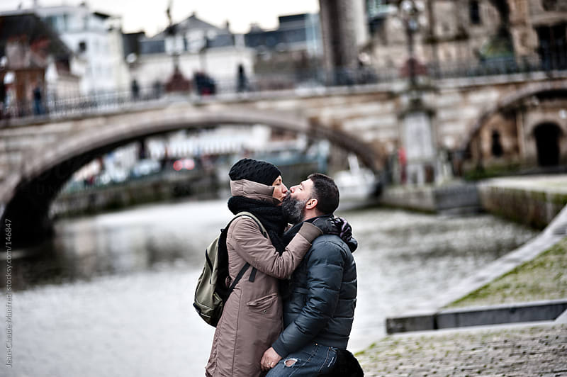 Young loving couple kissing on a walk along a canal by Jean-Claude Manfredi for Stocksy United