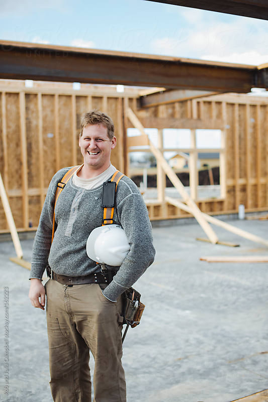 Portrait of smiling carpenter man at construction site by Rob and Julia Campbell for Stocksy United