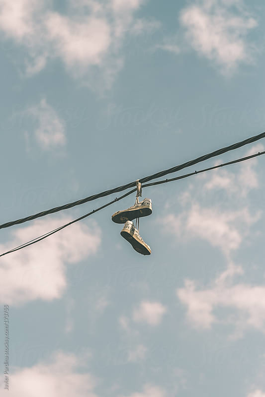 shoes hanging on the power line by Javier Pardina for Stocksy United