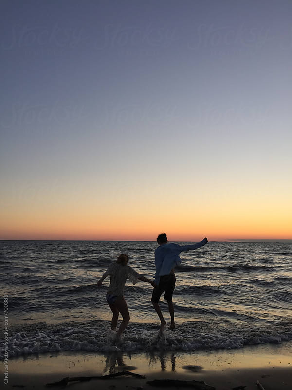 A young couple swimming at the beach at sunset by Chelsea Victoria for Stocksy United
