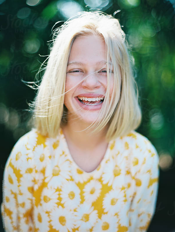 blonde girl laughing portrait in yellow floral dress by wendy laurel for Stocksy United