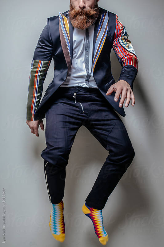 fashionable sexy hipster in colorful jacket and socks,jump by Igor Madjinca for Stocksy United