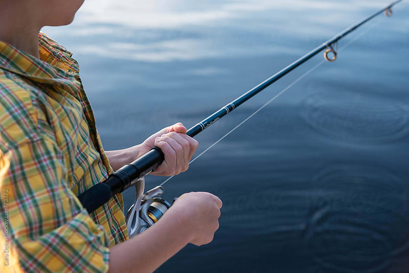 Boy reels in the line on his fishing pole at the lake by Cara Slifka for Stocksy United