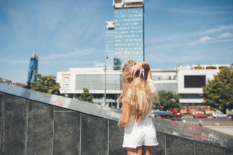 Young beautiful blond woman from the back in the city by Maja Topcagic for Stocksy United