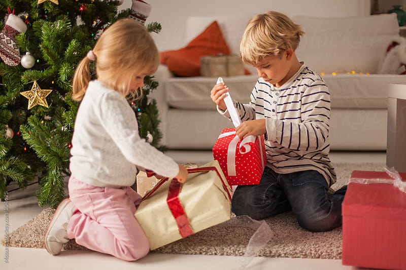 Children Opening Christmas Gifts at Home by Mosuno for Stocksy United