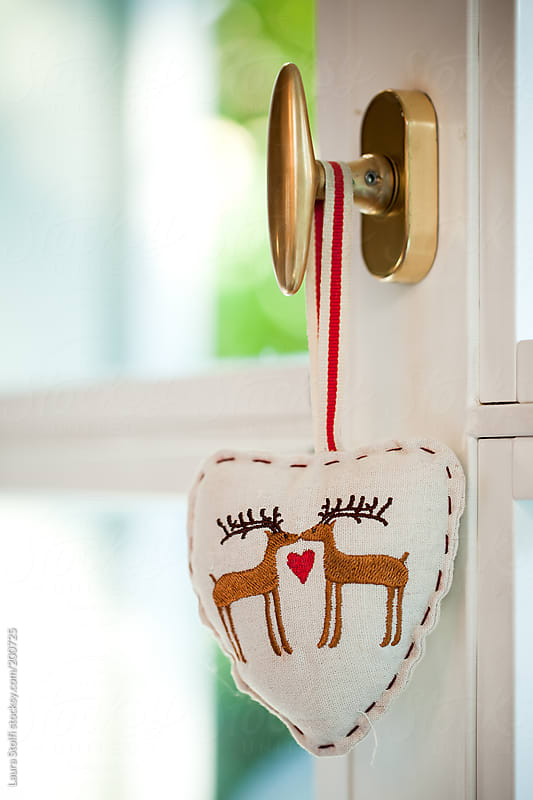 Heart shaped decoration with kissing reindeers on it hangs from door knob by Laura Stolfi for Stocksy United