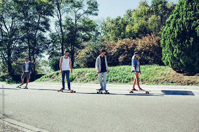Group of friends skateboarding outdoors by michela ravasio for Stocksy United