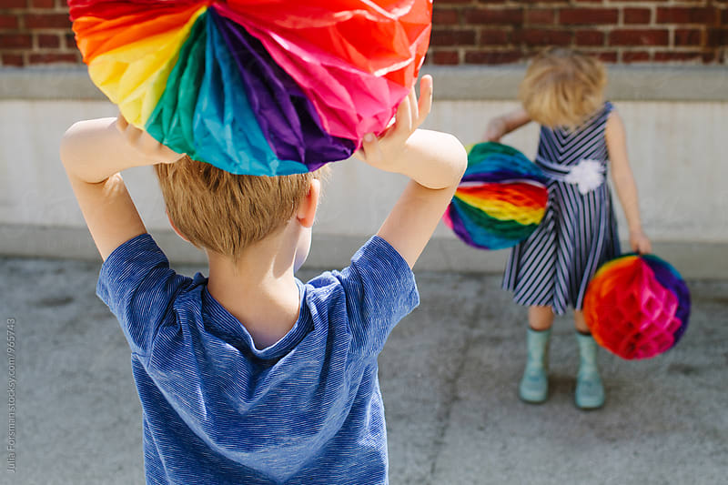 Two blonde kids hold colourful paper balls. by Julia Forsman for Stocksy United