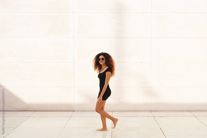Mulatto young woman walking against of white wall by Guille Faingold for Stocksy United