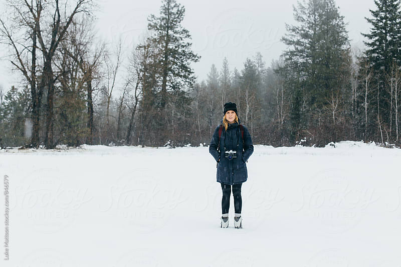 Young Blonde Woman Wearing Winter Clothes Standing In Snowy Meadow Surrounded By trees by Luke Mattson for Stocksy United