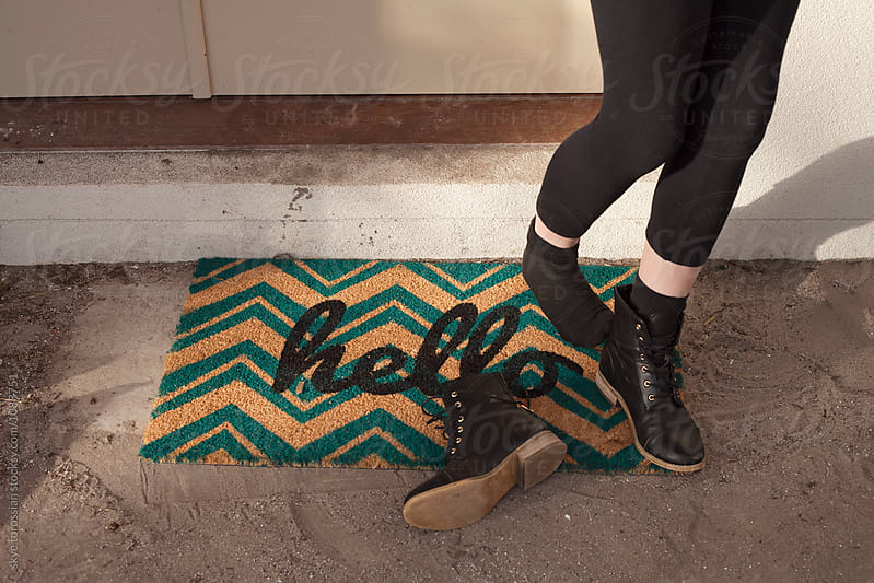 Girl at front door mat hello by skye torossian for Stocksy United