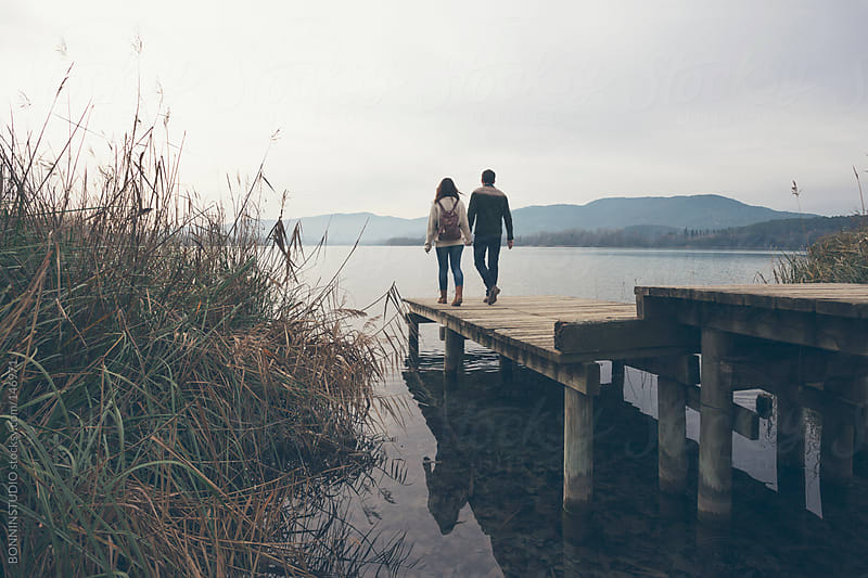 Young couple walking on wooden dock at the lakeshore. by BONNINSTUDIO for Stocksy United