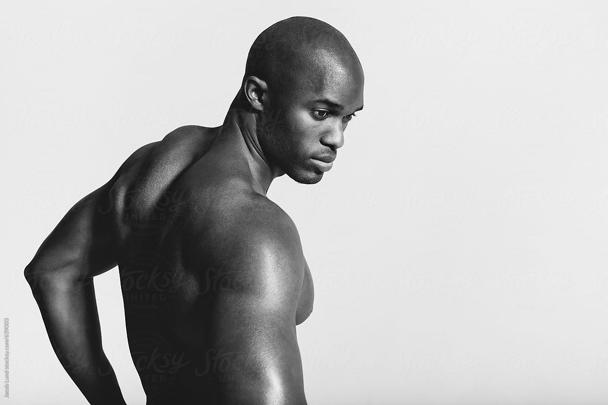 Rear view black and white shot of young man with muscular build looking over shoulder african shirtless male model