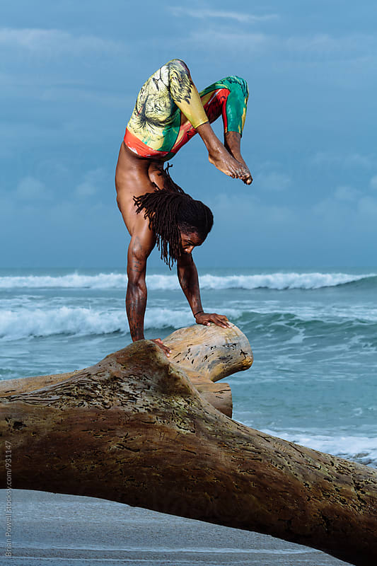athletic male Yoga on the beach by Brian Powell for Stocksy United