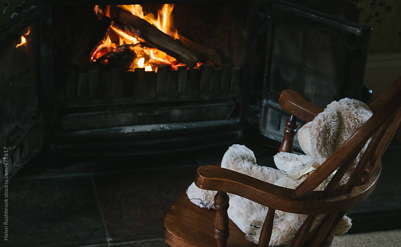An old teddy bear in a rocking chair on front of a fire. by Helen Rushbrook for Stocksy United