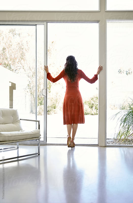 Woman standing in doorway looking out window by Trinette Reed for Stocksy United
