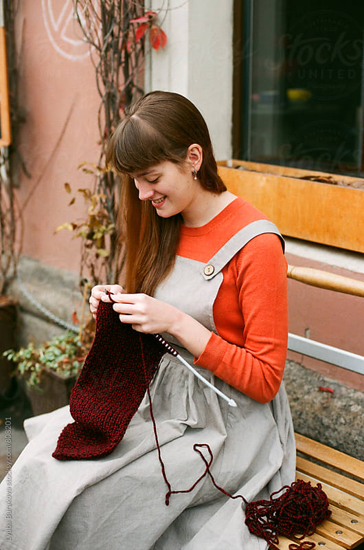 Young woman knitting outdoors by Liubov Burakova for Stocksy United