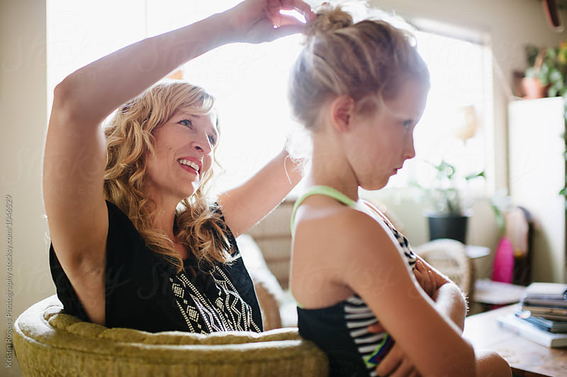 Mom in home doing daughters hair by Kristin Rogers Photography for Stocksy United