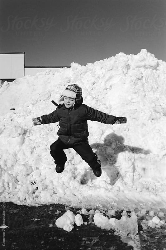 Boy Jumping From A Snow Plow Pile by Cameron Whitman for Stocksy United