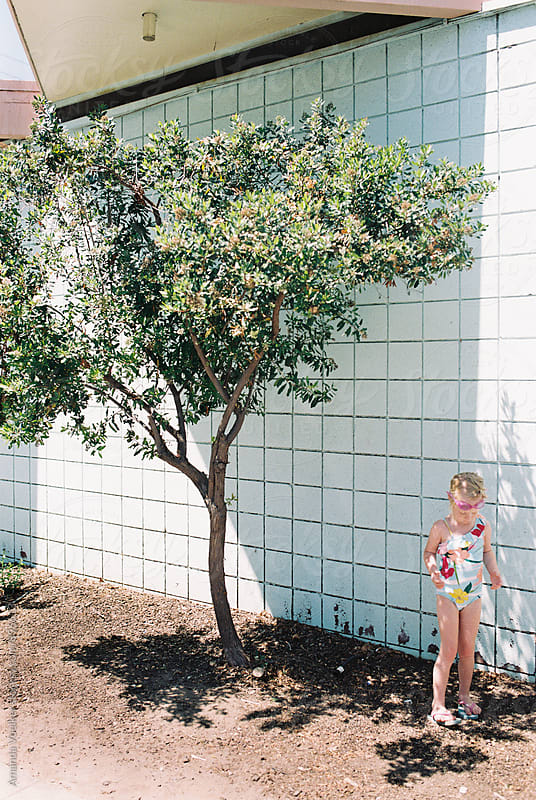 Little Girl in Swimsuit stands onder a tree by Amanda Voelker for Stocksy United