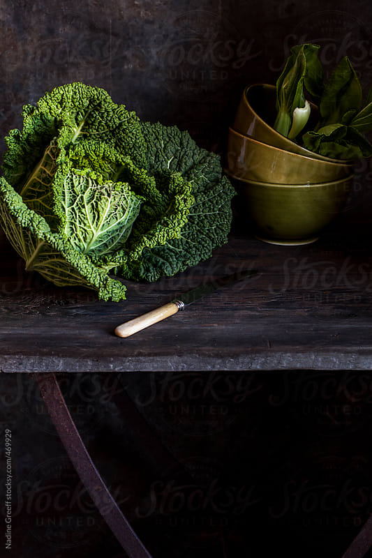 Savoy cabbage and bok choy on a rustic kitchen  table by Nadine Greeff for Stocksy United