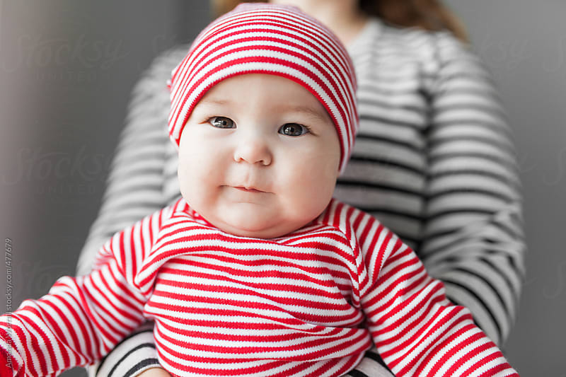 Close up of cute, chubby baby wearing striped Christmas pajamas by Amanda Worrall for Stocksy United