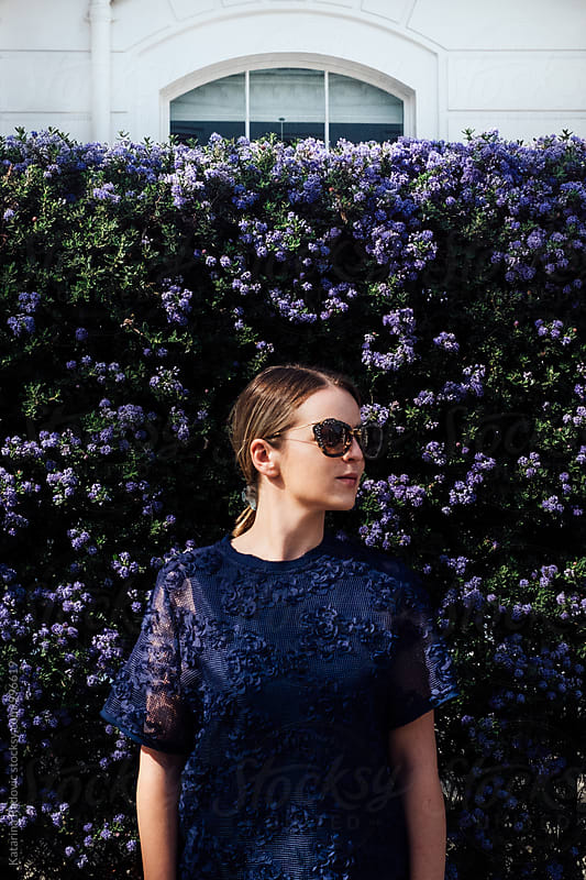 Beautiful Woman with Sunglasses Standing in front of the Purple Flower Wall by Katarina Radovic for Stocksy United