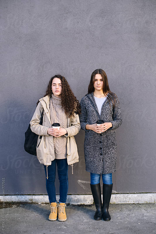 Two girlfriends standing against of grey wall outdoors by Danil Nevsky for Stocksy United