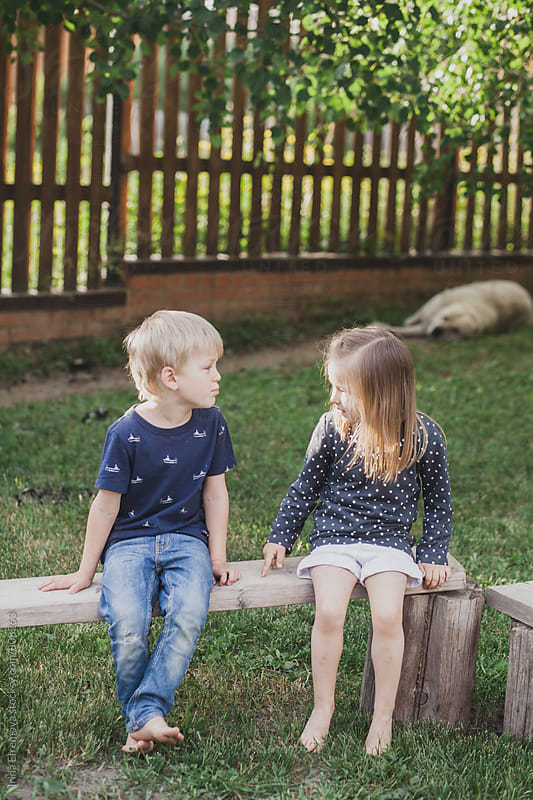 Cute kids couple sitting on the bench by Irina Efremova for Stocksy United