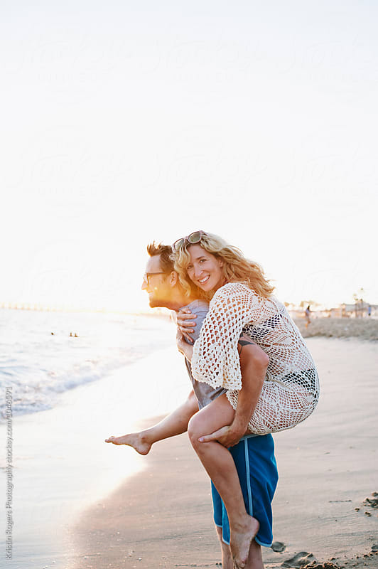 Husband giving his wife a piggyback ride on beach by Kristin Rogers Photography for Stocksy United