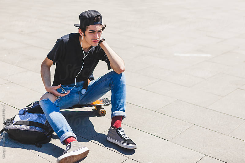 Teen Skater Listening to Music in the City by Giorgio Magini for Stocksy United