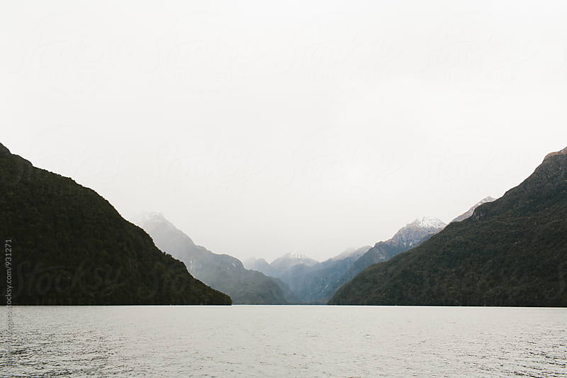 fog covered mountains on water by Cameron Zegers for Stocksy United