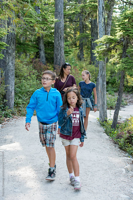 Fashionable Family Hiking In The Woods by Ronnie Comeau for Stocksy United