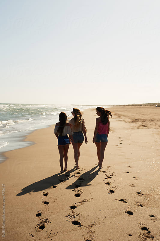 From behind: three young women at beachThree young girls on sunny beach leaving footprints on sand by Guille Faingold for Stocksy United