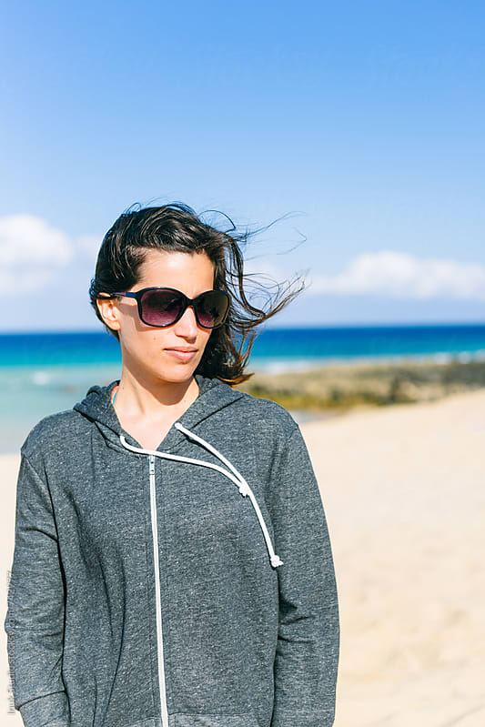 Casual woman in a windy beach, wearing sunglasses and a grey hoodie by Inuk Studio for Stocksy United