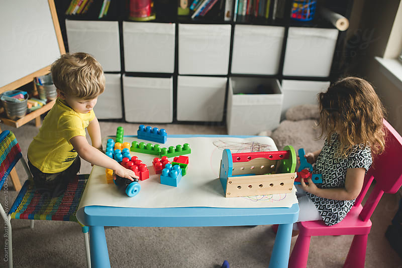 two little children building at home by Courtney Rust for Stocksy United