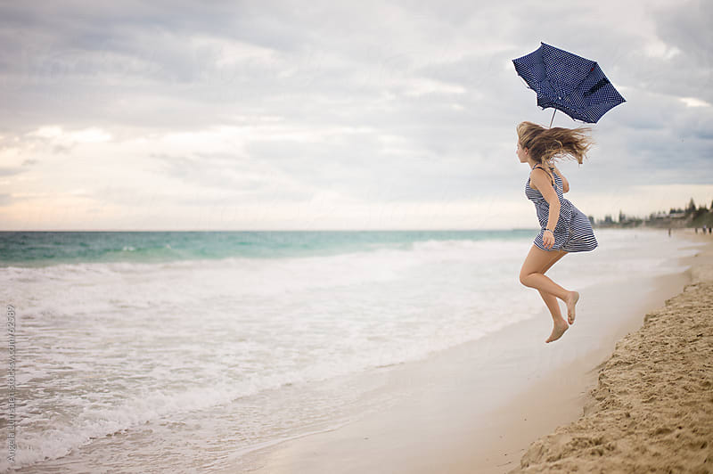 Girl leaping at the beach with an umbrella by Angela Lumsden for Stocksy United