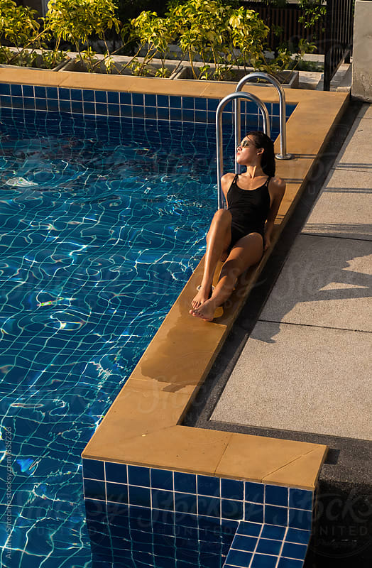 Attractive young female enjoying sun by the swimming pool. by Marko Milanovic for Stocksy United