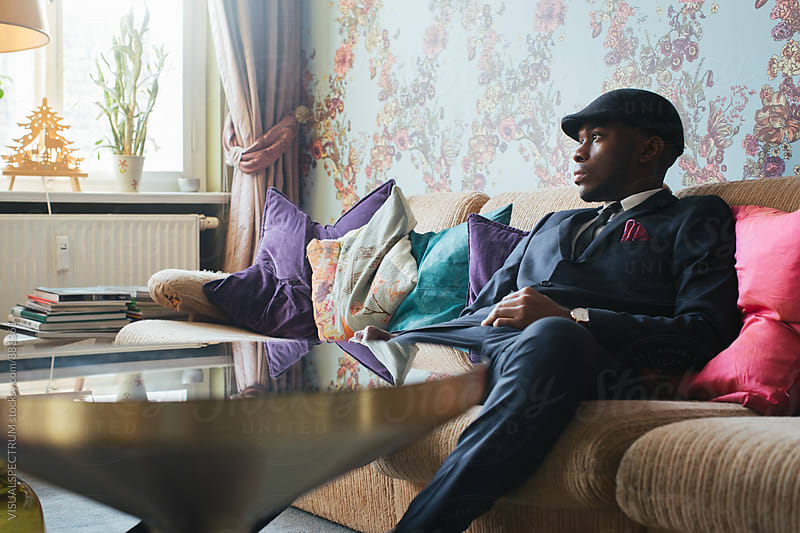 Elegantly Dressed Young Black Man Sitting on Sofa in Ornate Living Room by VISUALSPECTRUM for Stocksy United