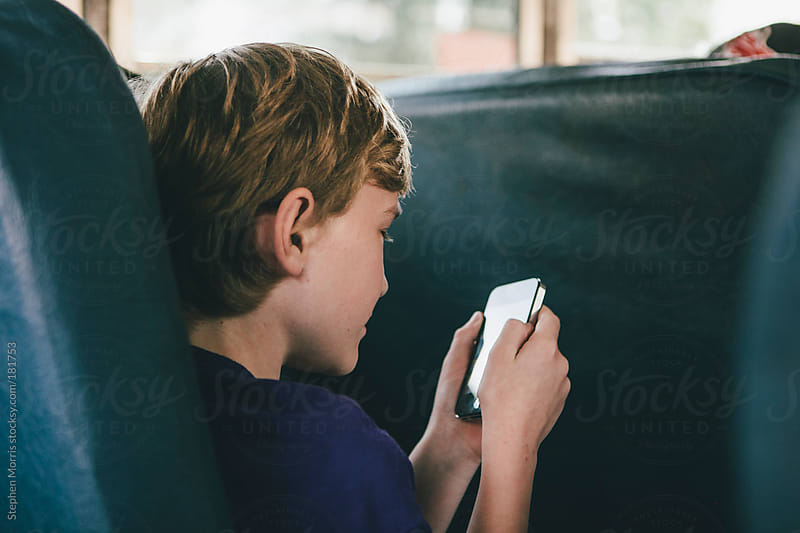 Boy on school bus using smart phone by Stephen Morris for Stocksy United