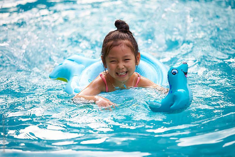 happy little asian girl in swimmnig pool by Bo Bo for Stocksy United