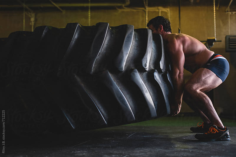 A strong man lifts a large tractor tire in a gym by Riley Joseph for Stocksy United